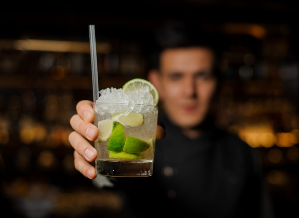 Bartender holding a glass filled with a fresh mojito